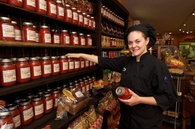 Bakery staff holding jar of signature sauce
